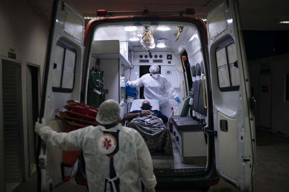 Mobile Emergency Care Service (SAMU) workers Gabrielle Carlos, top, and Joao Vericimo, move a COVID-19 patient to an ambulance as he is transferred to a municipal hospital dedicated to COVID-19 in Duque de Caxias, Rio de Janeiro state, Brazil, Tuesday, April 6, 2021. (AP Photo/Felipe Dana)