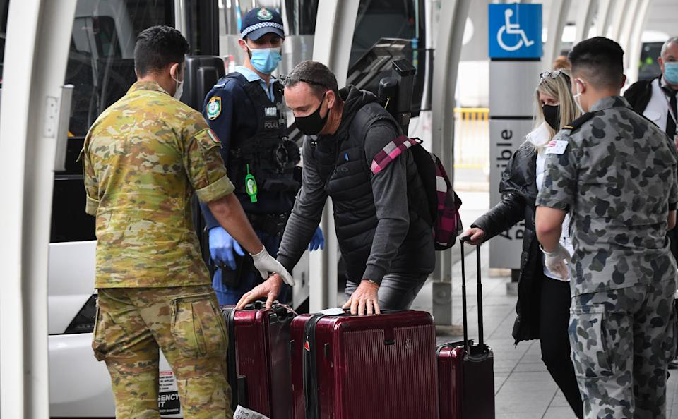 Passengers hand over their luggage to enter a hotel quarantine at Sydney International Airport on Aug. 8 in Australia. Authorities impose a mandatory hotel quarantine for 14 days for all arriving passengers. (Photo: James D. Morgan via Getty Images)