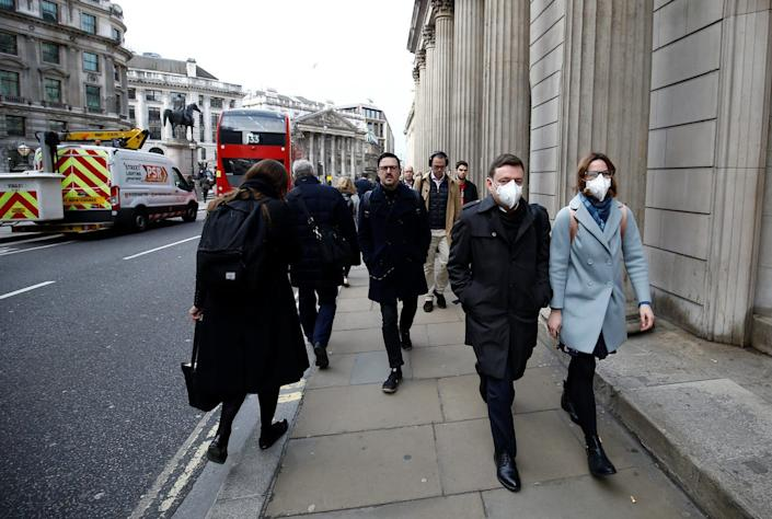 People wearing protective face masks walk on a street, following an outbreak of the coronavirus, in London, Britain March 11, 2020. REUTERS/Henry Nicholls