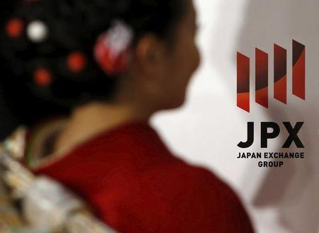 A logo of Japan Exchange Group Inc. is seen next to a woman, dressed in ceremonial kimono at the Tokyo Stock Exchange (TSE),  in Tokyo, Japan, January 4, 2016.   REUTERS/Yuya Shino/File Photo