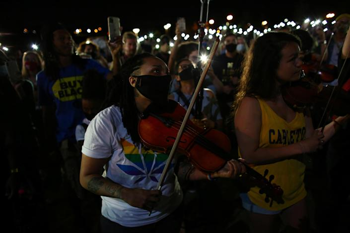 At a vigil in Aurora, Colorado, on June 27, 2020,Valerie Reives plays the viola while protesters shine their mobile phone lights to honor Elijah McClain who, when alive, would play his violin at animal shelters because he thought the kittens were lonely. / Credit: KEVIN MOHATT / REUTERS