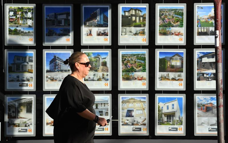 A woman walks past a real estate agent's window advertising houses for sale and auction in Melbourne on May 1, 2019. - Australian property prices fell faster in the past year than at any time since the global financial crisis, a closely watched report said May 1, fuelling speculation of a pre-election interest rate cut. (Photo by William WEST / AFP) (Photo credit should read WILLIAM WEST/AFP via Getty Images)