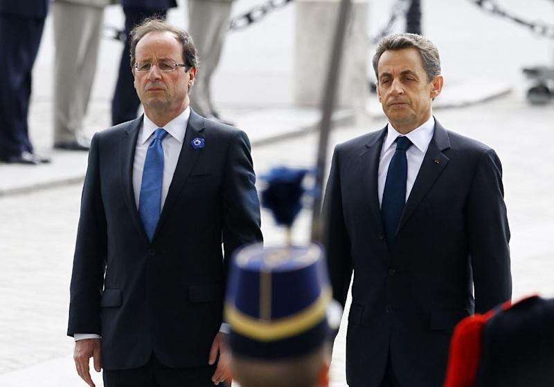 In this May 8, 2012 photo, outgoing French President Nicolas Sarkozy, right, and President-elect Francois Hollande observe a minute of silence at the Tomb of the Unknown Soldier during commemorations at the Arc de Triomphe in Paris. The elections that drove Sarkozy out of power in France and left Greece scrambling to build a coalition government pose a financial threat to the United States that could undermine President Barack Obama's efforts to cast himself as the agent of a U.S. economic revival. That could feed Mitt Romney's argument that the economy under Obama is too weak to sustain a financial shock from across the Atlantic. (AP Photo/Francois Mori, Pool)