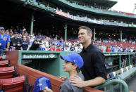 FILE - In this April 28, 2017, file photo, Theo Epstein, president of baseball operations for the Chicago Cubs, poses with a young fan prior to a baseball game between the Boston Red Sox and the Cubs at Fenway Park in Boston. Theo Epstein, who transformed the long-suffering Chicago Cubs and helped bring home a drought-busting championship in 2016, is stepping down after nine seasons as the club's president of baseball operations. The team announced Monday, Nov. 16, 2020, Epstein is leaving the organization, and general manager Jed Hoyer is being promoted to take his place. (AP Photo/Elise Amendola, File)