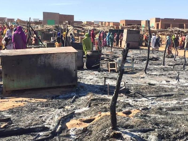 Residents of a refugee camp gather around the burned remains of makeshift structures, in Genena, Sudan: AP