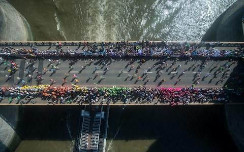 Runners cross over Tower Bridge - Credit: GETTY IMAGES
