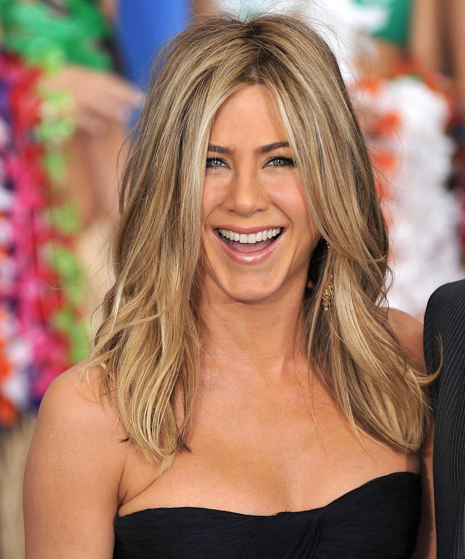 """<h3>2011: Zig-Zag Part</h3><br>Aniston's slightly askew hair part is the perfect complement to her <a href=""""https://www.refinery29.com/en-us/2019/11/8704914/smokey-gold-hair-color-trend"""" rel=""""nofollow noopener"""" target=""""_blank"""" data-ylk=""""slk:beachy blonde highlights."""" class=""""link rapid-noclick-resp"""">beachy blonde highlights.</a><span class=""""copyright"""">Photo: James Devaney/WireImage.</span>"""