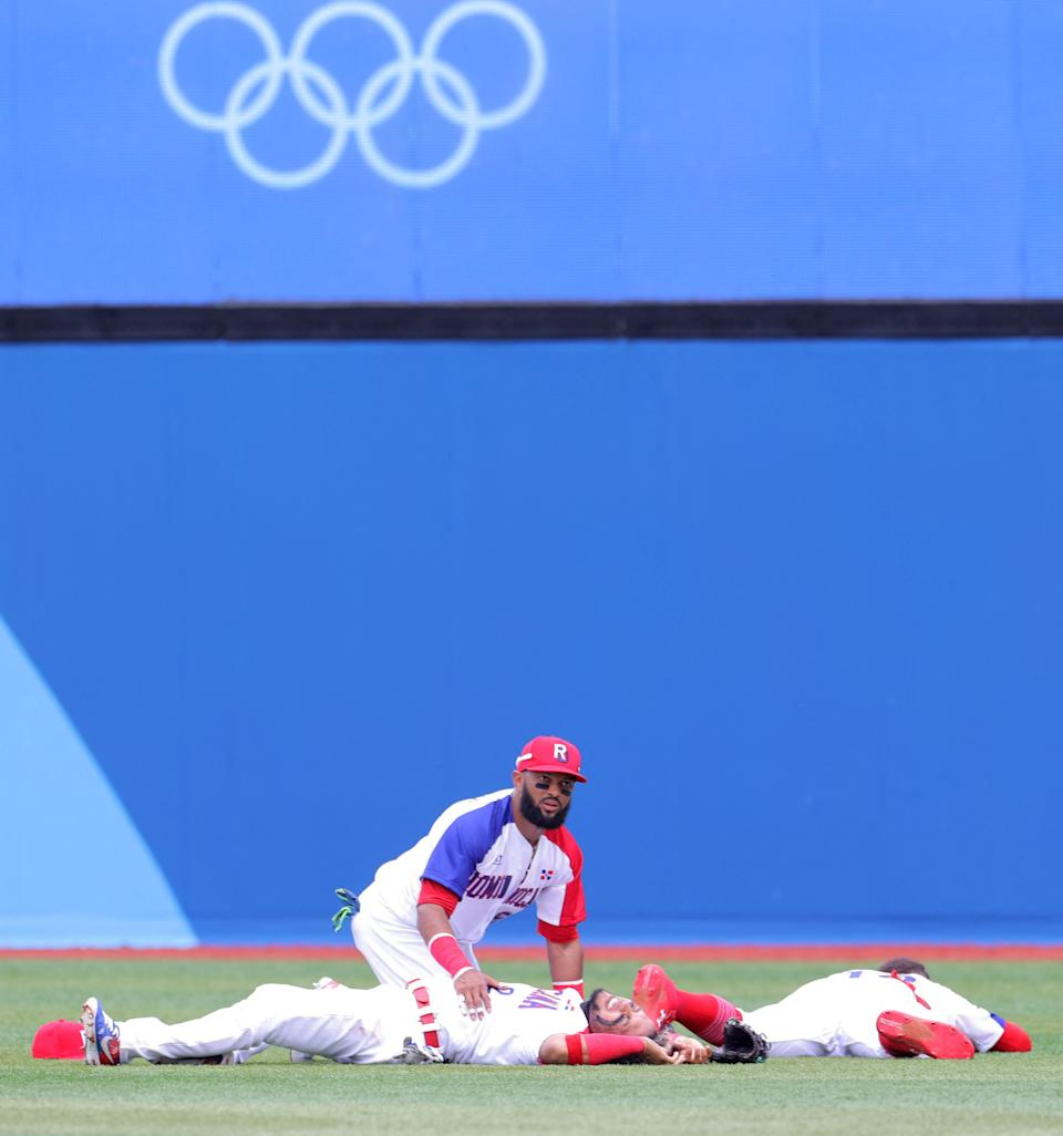 Dominican Republic's centre fielder Emilio Bonifacio (C) comforts second baseman Gustavo Nunez (bottom L) after collided with right fielder Julio Rodriguez (bottom R) while catching a pop fly by Mexico's Ramiro Pena (not in photo) during the third inning of the Tokyo 2020 Olympic Games baseball opening round group A game between Mexico and Dominican Republic at Yokohama Baseball Stadium in Yokohama, Japan, on July 30, 2021. (Photo by KAZUHIRO FUJIHARA / AFP) (Photo by KAZUHIRO FUJIHARA/AFP via Getty Images)