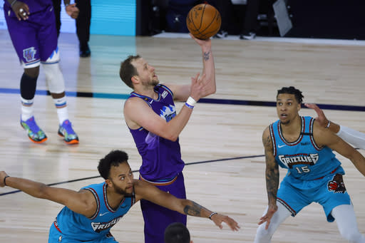 Utah Jazz's Joe Ingles, center, draws a foul on Memphis Grizzlies' Kyle Anderson, left, during the first half of an NBA basketball game Wednesday, Aug. 5, 2020, in Lake Buena Vista, Fla. (Kevin C. Cox/Pool Photo via AP)