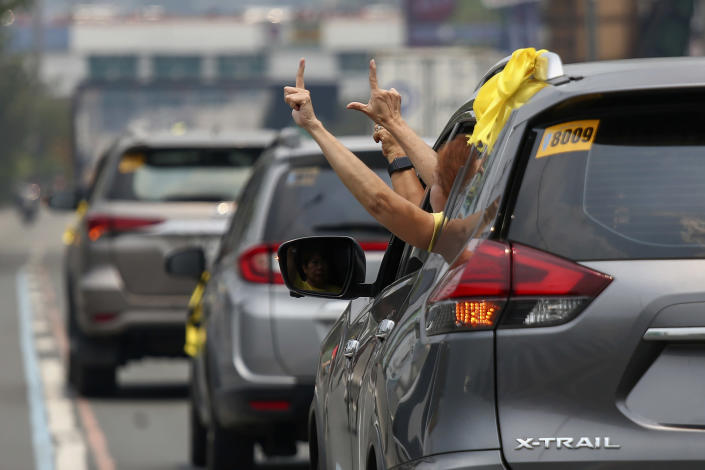 """Supporters of former Philippine President Benigno Aquino III flash the """"L"""" sign meaning """"Fight!"""" from a vehicle window during a motorcade before his burial in Quezon City, Philippines on Saturday, June 26, 2021. Aquino was buried in austere state rites during the pandemic Saturday with many remembering him for standing up to China over territorial disputes, striking a peace deal with Muslim guerrillas and defending democracy in a Southeast Asian nation where his parents helped topple a dictator. He was 61. (AP Photo/Basilio Sepe)"""