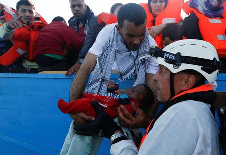 A migrant hands a baby from a wooden boat to a rescuer of the Malta-based NGO Migrant Offshore Aid Station (MOAS) during a rescue operation in the central Mediterranean in international waters off the coast of Sabratha in Libya, April 15, 2017.    REUTERS/Darrin Zammit Lupi