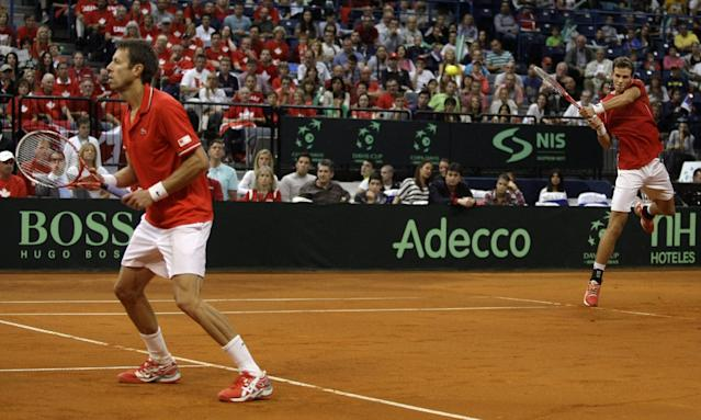 Canada's Vasek Pospisil, right, returns a ball as Daniel Nestor follows the action during their Davis Cup semifinal tennis doubles match against Serbia's Nenad Zimonjic and Ilija Bozoljac in Belgrade, Serbia, Saturday, Sept. 14, 2013. (AP Photo/Marko Drobnjakovic)