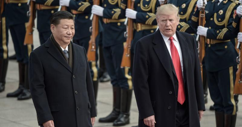 China's President Xi Jinping (L) and US President Donald Trump review Chinese honour guards during a welcome ceremony at the Great Hall of the People in Beijing on November 9, 2017.