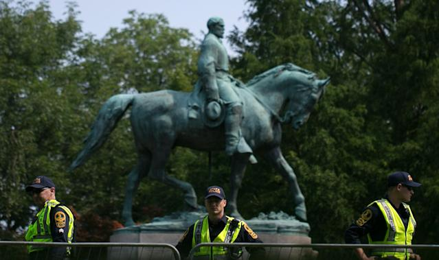 <p>Virginia State Police guard the statue of Confederate Robert E. Lee on August 12, 2018 in downtown Charlottesville, Virginia, on the one-year anniverary of the violent Unite the Right rally that left one person dead and dozens injured. – Last year's protests in Charlottesville saw hundreds of neo-Nazi sympathizers, accompanied by rifle-carrying men, yelling white nationalist slogans and wielding flaming torches in scenes eerily reminiscent of racist rallies held in America's South before the Civil Rights movement. (Photo: Logan Cyrus/AFP/Getty Images) </p>