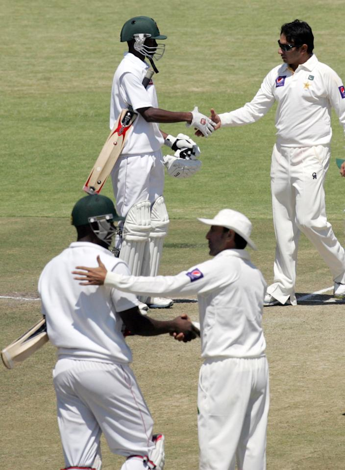 Zimbabwe batsman shake hands with Pakistan players after conceeding defeat during the fifth day of the first test match between Pakistan and hosts Zimbabwe at the Harare Sports Club on September 7, 2013. AFP PHOTO / JEKESAI NJIKIZANA        (Photo credit should read JEKESAI NJIKIZANA/AFP/Getty Images)