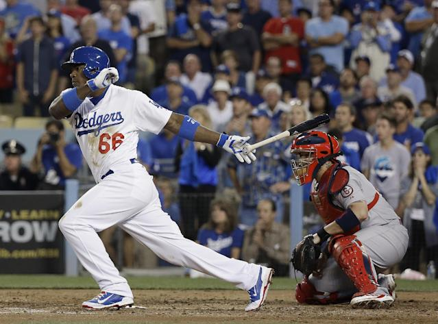 Los Angeles Dodgers' Yasiel Puig hits an RBI single during the fourth inning of Game 4 of the National League baseball championship series against the St. Louis Cardinals Tuesday, Oct. 15, 2013, in Los Angeles. (AP Photo/David J. Phillip)