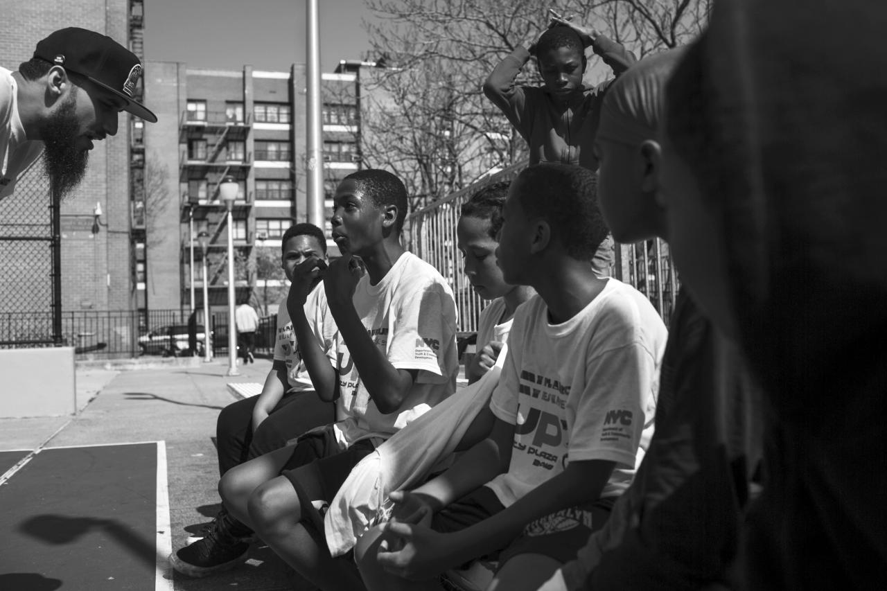 <p>Brother Curley of the ManUp cure violence team coaches kids during a basketball game organized by ManUp for the community of E. New York. (Photograph by Amnon Gutman) </p>