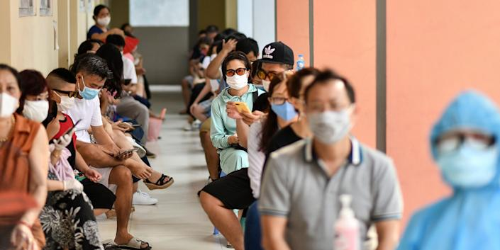 Residents wait to be tested at a makeshift rapid testing centre as Vietnam records a rise in cases of the COVID-19 coronavirus in Hanoi on July 31, 2020.