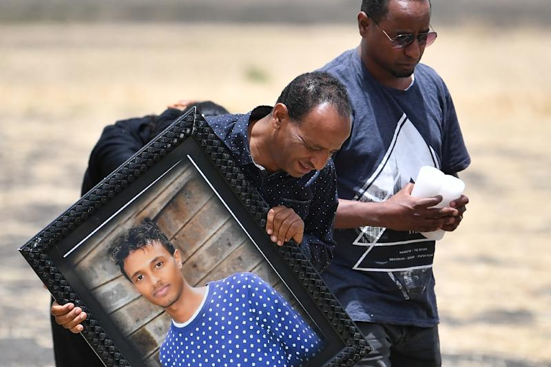 Some mourners carried pictures of their loved-ones (AFP Photo/TONY KARUMBA)