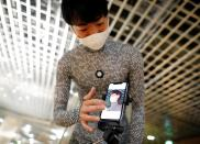 An employee of online fashion retailer Zozo Inc. demonstrates the company's Zozosuit 2, a 3D body measurement suit, in Tokyo