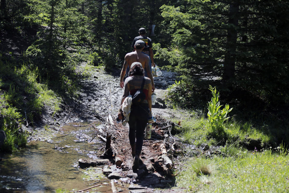Rainbow Gathering participants walk across a creek using a handmade bridge on Friday, July 2, 2021, in the Carson National Forest, outside of Taos, N.M. More than 2,000 people have made the trek into the mountains of northern New Mexico as part of an annual counterculture gathering of the so-called Rainbow Family. While past congregations on national forest lands elsewhere have drawn as many as 20,000 people, this year's festival appears to be more reserved. Members (AP Photo/Cedar Attanasio)