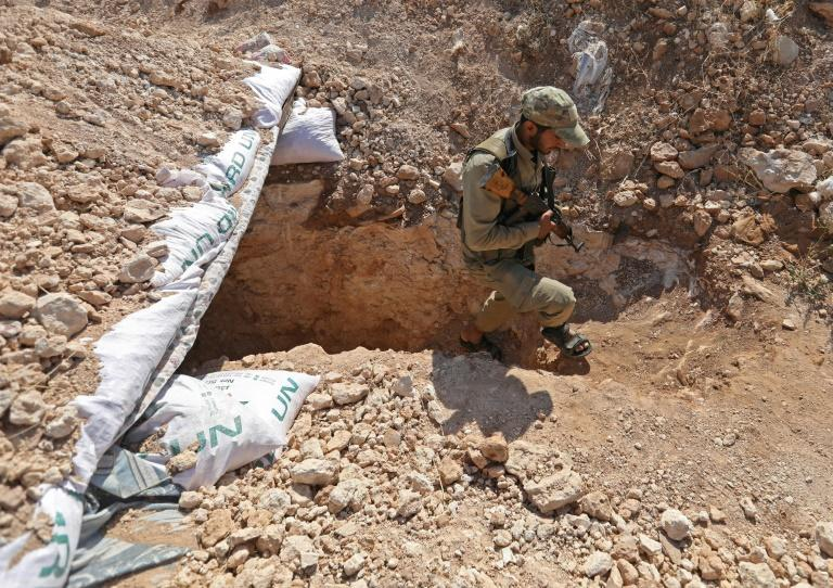 A Syrian rebel fighter emerges from a freshly-dug trench in Idlib province as anti-government forces prepare for an expected regime assault