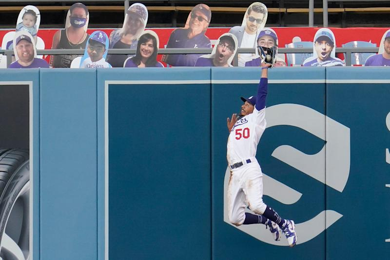 Los Angeles Dodgers right fielder Mookie Betts leaps and makes the catch on a ball hit by Colorado Rockies' Kevin Pillar during the second inning of a baseball game Saturday, Sept. 5, 2020, in Los Angeles.