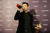 """Singapore director Anthony Chen kisses one of his awards, and poses for the media, after winning the Best New Director and the Best Original Screenplay awards, at the 50th Golden Horse Awards in Taipei, Taiwan, Saturday, Nov. 23, 2013. Chen won for the film """" Ilo.Ilo """" at this year's Golden Horse Awards -the Chinese-language film industry's biggest annual events. (AP Photo/Wally Santana)"""