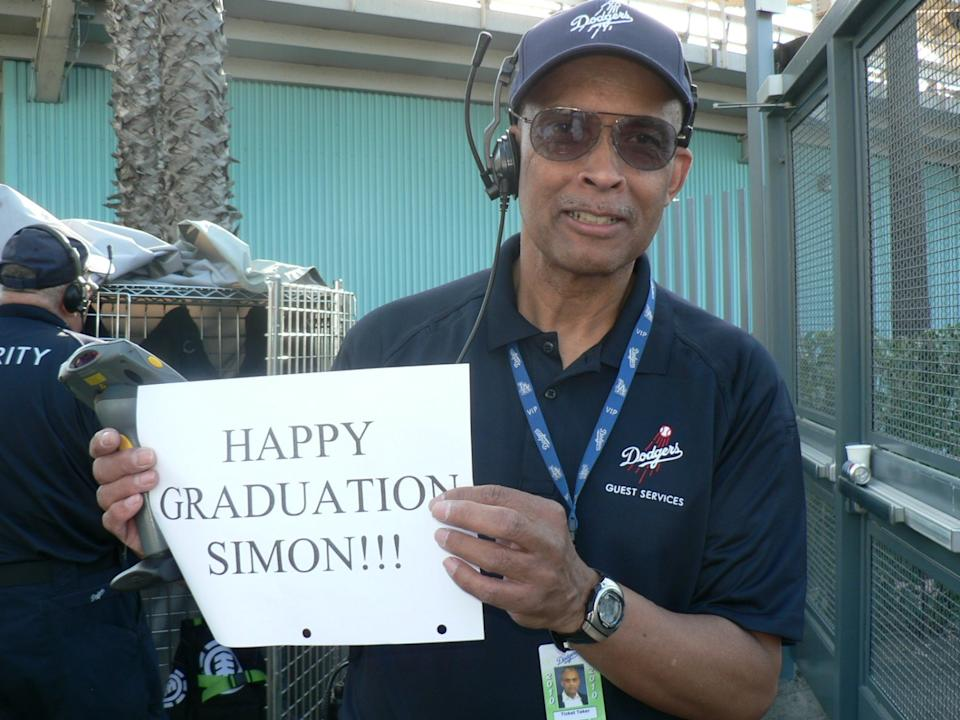 Dodger Stadium worker Errol Coffey wishes a happy high school graduation to Dodgers fan Simon Brooks.