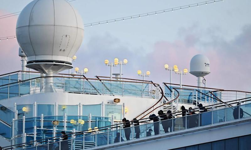Some of the remaining quarantined passengers look out from the deck of the Diamond Princess