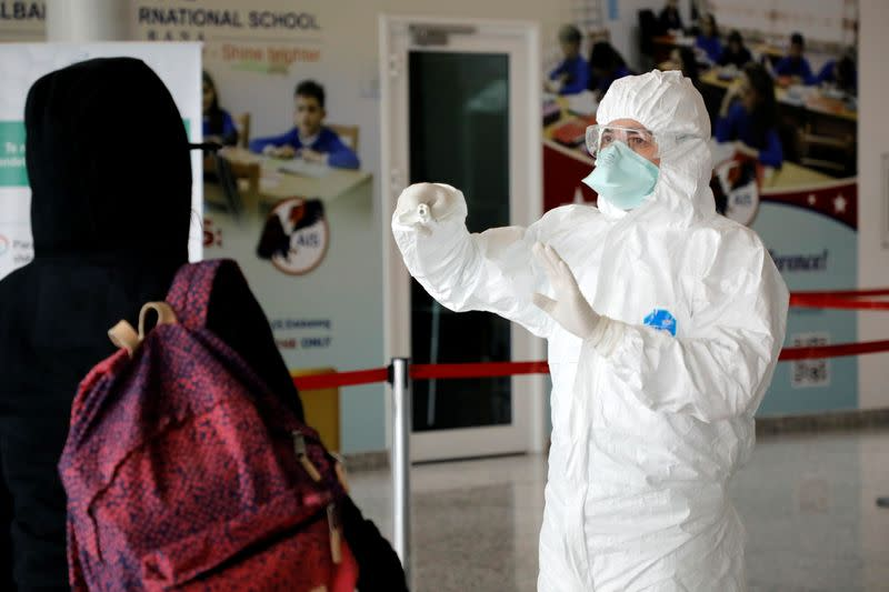 Medical staff member, wearing protective suit, gestures at Tirana International Airport