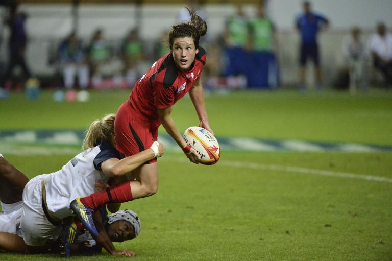 Canadian full back Elissa Alarie (R) is tackled by French players during the IRB Women's Rugby World Cup match between France and Canada at the Jean Bouin Stadium, on August 13, 2014 in Paris (AFP Photo/Fred Dufour)