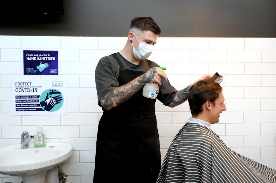 AUCKLAND, NEW ZEALAND - MAY 14:  A Barber wearing a face mask works on a customer's hair at Board & Blade Barbour Shop on May 14, 2020 in Auckland, New Zealand. New Zealand moves to COVID-19 Alert Level 2 in three stages starting from today with restaurants, cinemas, retail, playgrounds and gyms able to reopen with physical distancing and strict hygiene measures in place. Public gatherings are permitted for up to 10 people and New Zealanders are now able to travel domestically. Schools and early childhood centres will open from Monday 18 May while bars will be allowed to reopen from Thursday 21 May. New Zealand was placed under full lockdown on March 26 in response to the coronavirus (COVID-19) pandemic. (Photo by Hannah Peters/Getty Images)