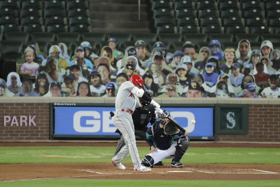 Los Angeles Angels' Shohei Ohtani hits a solo home run as Seattle Mariners catcher Joe Hudson looks on during the second inning of a baseball game, Thursday, Aug. 6, 2020, in Seattle. (AP Photo/Ted S. Warren)