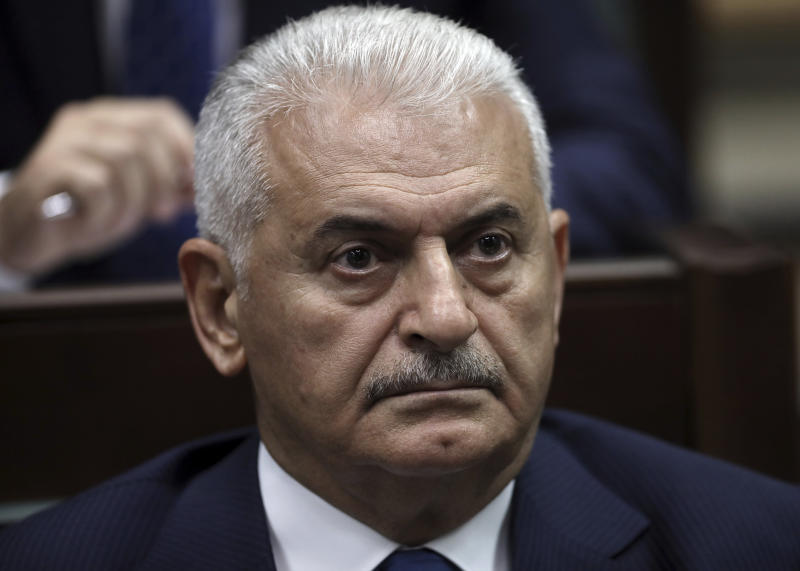 Binali Yildirim, ruling Justice and Development Party's mayoral candidate for Istanbul, listens to President Recep Tayyip Erdogan at the parliament in Ankara, Turkey, Tuesday, June 25, 2019, two days after Ekrem Imamoglu, the candidate of the secular opposition Republican People's Party, won the election for mayor of Istanbul. Erdogan addressed his AK Party's weekly meeting, the first time he speaks since the Istanbul mayoral election Sunday, which was a big setback for him and his party. (AP Photo/Burhan Ozbilici)