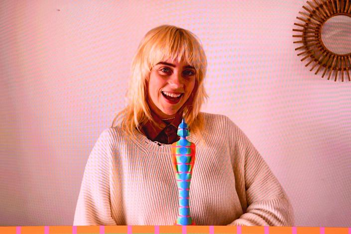"""While Billie wasn't in attendance, she did make an appearance to accept her award for Best International Female Solo Artist via video call. Fresh-faced and <a href=""""https://www.teenvogue.com/story/billie-eilish-blonde-inspiration?mbid=synd_yahoo_rss"""" rel=""""nofollow noopener"""" target=""""_blank"""" data-ylk=""""slk:sporting her newly blonde hair"""" class=""""link rapid-noclick-resp"""">sporting her newly blonde hair</a>, she had on a cozy cream ribbed sweater and a brown collared shirt underneath."""