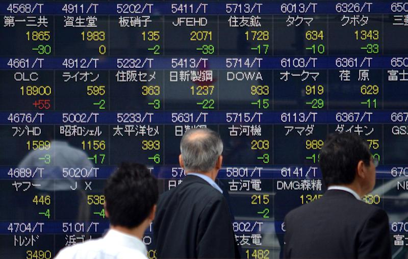 Pedestrians walk past a share price board of the Tokyo Stock Exchange on July 18, 2014