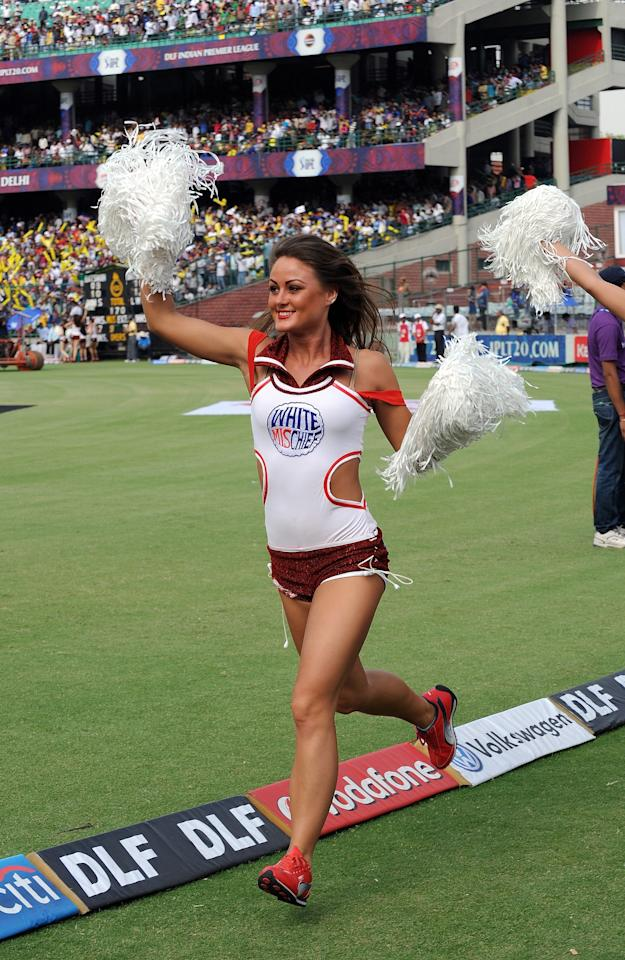 A Delhi Daredevils cheerleader girl runs around the score boundary before the starrt of the IPL Twenty20 cricket match between Delhi Daredevils and Rajasthan Royals at the Feroz Shah Kotla stadium in New Delhi on April 29, 2012.  RESTRICTED TO EDITORIAL USE. MOBILE USE WITHIN NEWS PACKAGE.    AFP PHOTO/Prakash SINGH        (Photo credit should read PRAKASH SINGH/AFP/GettyImages)