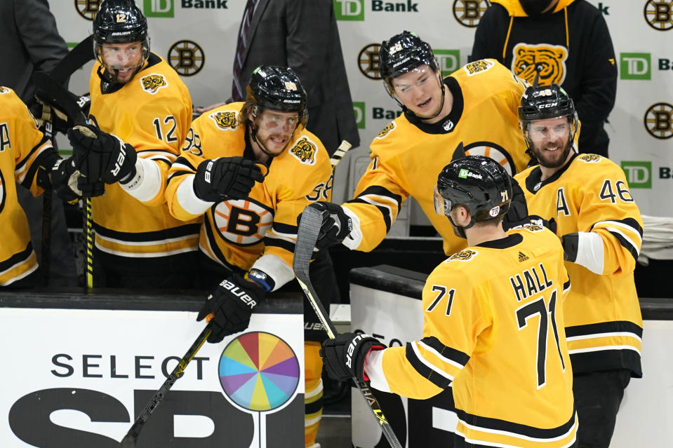 Boston Bruins left wing Taylor Hall (71) celebrates his goal with teammates on the bench in the third period of an NHL hockey game against the New York Islanders, Thursday, April 15, 2021, in Boston. (AP Photo/Elise Amendola)