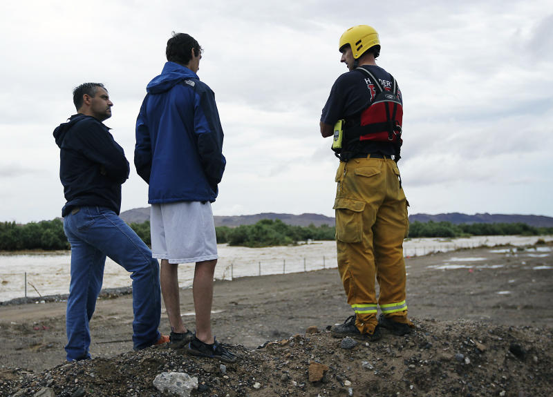 Witnesses Steven Faubel, left, and Justin Faubel, middle, share information with Henderson fireman Robert Uszynski near the Duck Creek Channel during a search for a missing teenager in Henderson, Nev., on Wednesday, Aug. 22, 2012. According to witnesses, the man was pulled into the heavily flooded wash as intense thunderstorms filled storm channels and sent water into roadways. (AP Photo/Las Vegas Review-Journal, Jason Bean) LOCAL TV OUT; LOCAL INTERNET OUT; LAS VEGAS SUN OUT