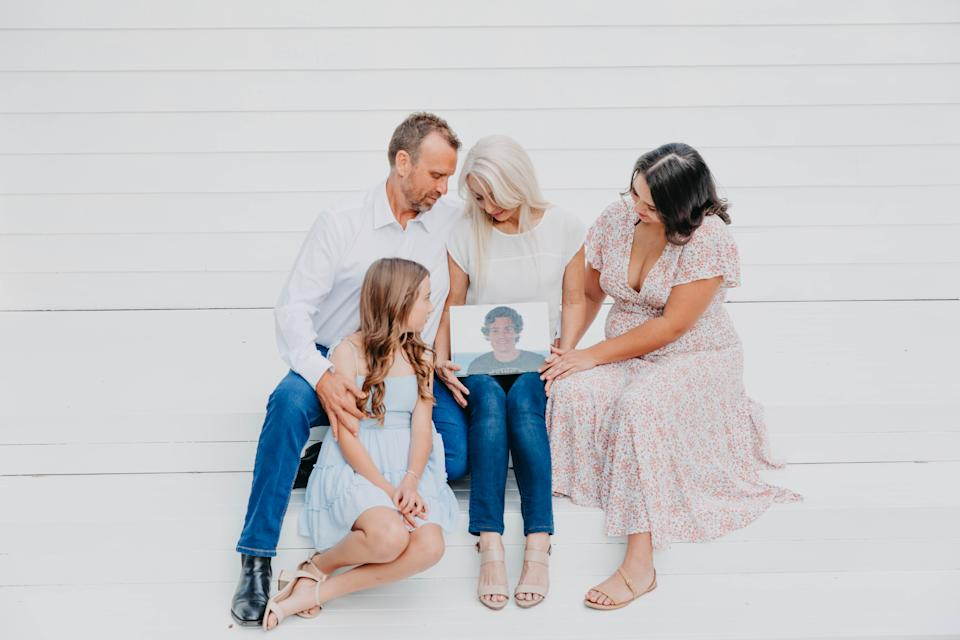 Melissa and Peter McGuinness and their two daughters gather around a photo of Jordan.
