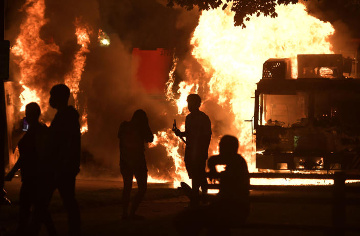 Garbage and dump trucks were set ablaze on Sunday, Aug. 23, 2020 by rioters near the Kenosha County Courthouse where they had been set up to prevent damage to the building. The building was still damaged and was closed on Monday. (Sean Krajacic/Kenosha News via AP)