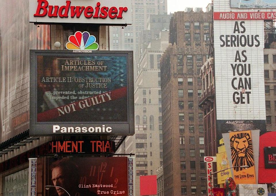 The NBC jumbotron in Times Square displays the 'not guilty' verdict on the obstruction of justice charges against Bill Clinton during his impeachment trial on 12 February 1999. The Senate acquitted Clinton on charges of perjury and obstruction of justice (TIMOTHY A CLARY/AFP via Getty Images)