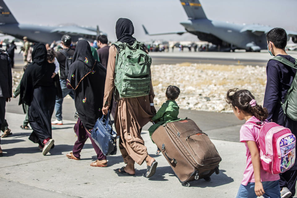 In this image provided by the U.S. Marine Corps, families walk towards their flight during ongoing evacuations at Hamid Karzai International Airport, Kabul, Afghanistan, Tuesday, Aug. 24, 2021. (Sgt. Samuel Ruiz/U.S. Marine Corps via AP)