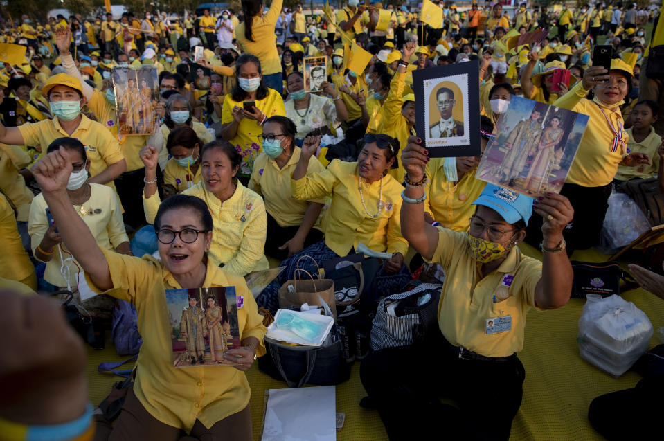 Supporters of Thai monarch display images of King Maha Vajiralongkorn, Queen Suthida and late King Bhumibol Adulyadej ahead of the arrival of king and queen to participate in a candle lighting ceremony to mark birth anniversary of late King Bhumibol Adulyadej at Sanam Luang ceremonial ground in Bangkok, Thailand, Saturday, Dec. 5, 2020. (AP Photo/Gemunu Amarasinghe)