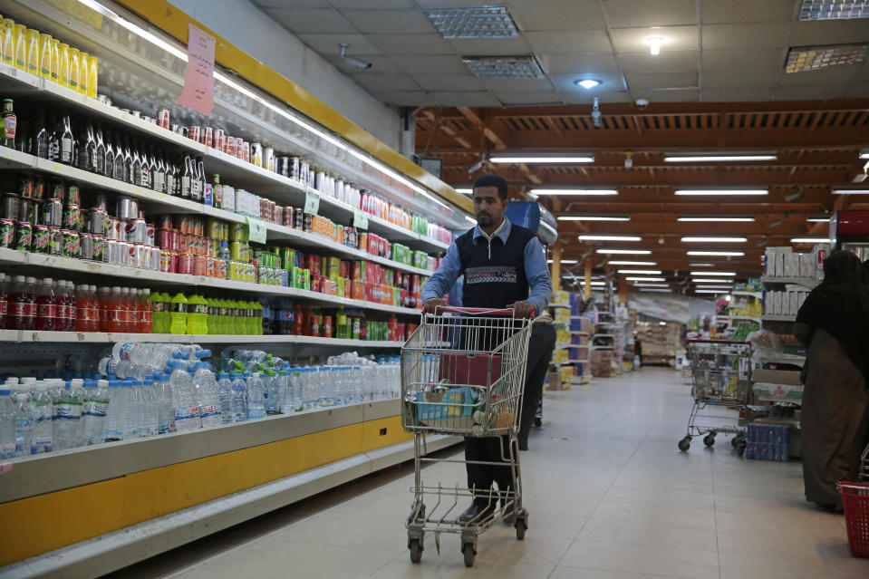 A worker removes French products from a supermarket, in Sanaa, Yemen, Monday, Oct. 26, 2020. Muslims in the Middle East and beyond on Monday called for boycotts of French products and for protests over caricatures of the Prophet Muhammad they deem insulting and blasphemous, but France's president has vowed his country will not back down from its secular ideals and defense of free speech. (AP Photo/Hani Mohammed)