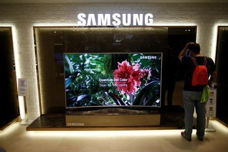 "A man stands next to a Samsung Electronics ""Quantum Dot"" SUHD television at its headquarters in Seoul, South Korea, July 4, 2016. REUTERS/Kim Hong-Ji"