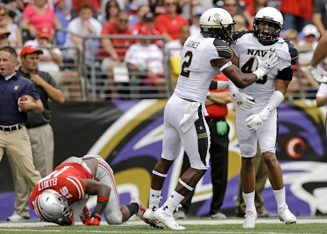 Navy safety Parrish Gaines (2) and linebacker Chris Johnson celebrate after Johnson stopped Ohio State running back Ezekiel Elliott, bottom left, on a third and goal attempt in the first half of an NCAA college football game in Baltimore, Saturday, Aug. 30, 2014. (AP Photo/Patrick Semansky)