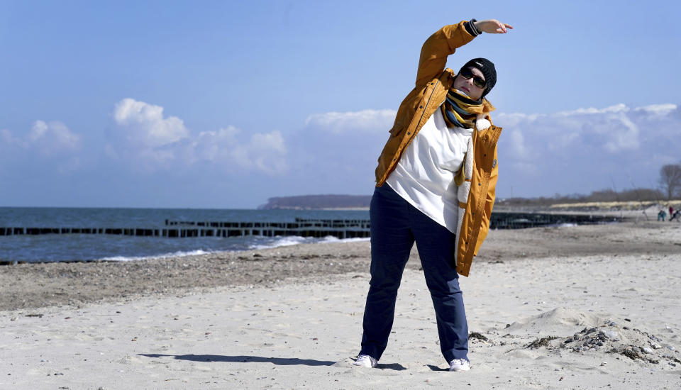 Simone Ravera, patient of the 'MEDIAN Clinic Heiligendamm', makes exercises after an interview with the Associated Press in Heiligendamm, northern Germany, Wednesday, April 14, 2021. The MEDIAN Clinic, specialized on lung diseases, treats COVID-19 long time patients from all over Germany. (AP Photo/Michael Sohn)