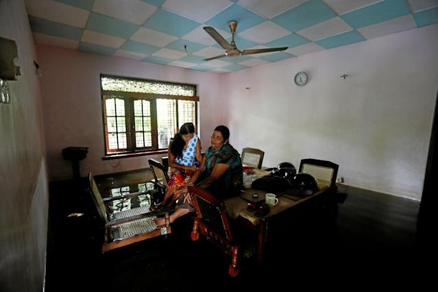 <p>A family sits on a table inside their flooded house in Nagoda village in Kalutara, Sri Lanka, May 29, 2017. (Dinuka Liyanawatte/Reuters) </p>